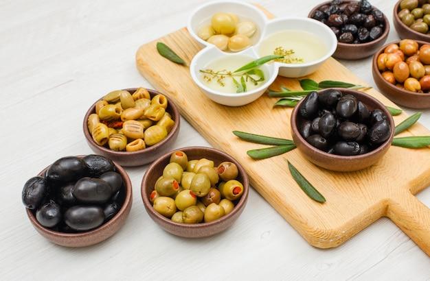 Olive e olio d'oliva marinati con le foglie di ulivo in ciotole e tagliere su legno bianco, vista dell'angolo alto.