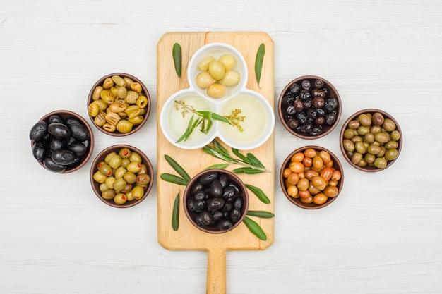 Olive e olio d'oliva marinati in ciotole e tagliere con la vista superiore delle foglie di ulivo su legno bianco