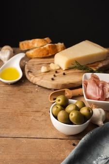 Olive e prosciutto di parmigiano dell'angolo alto sul tagliere