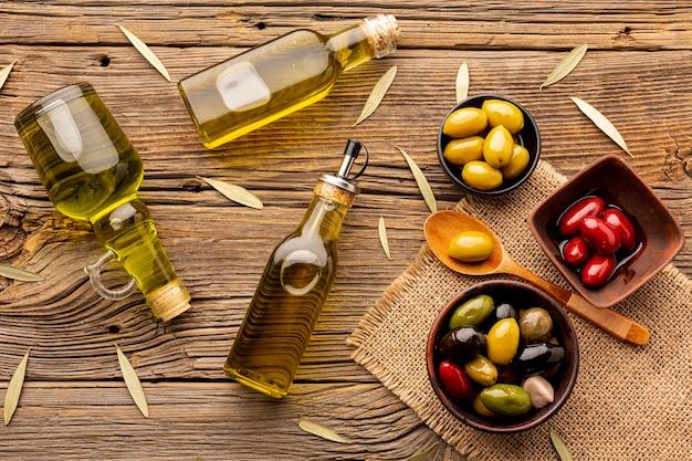 Olive in ciotole bottiglie di olio e foglie su materiale tessile