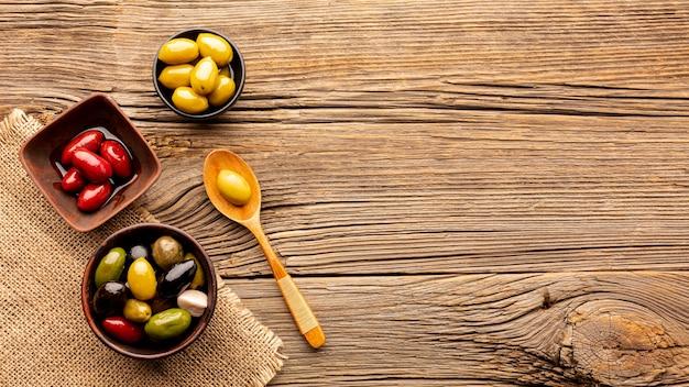 Olive in ciotole e cucchiaio di legno con spazio di copia