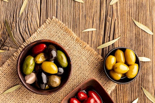 Olive in ciotole e foglie su materiale tessile