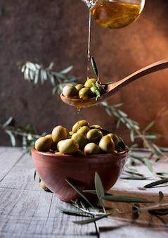 Olive in cucchiaio di legno versando olio sopra la ciotola piena di olive con l'osso