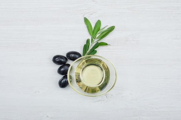 Olive nere e olio d'oliva in una latta di vetro con la vista superiore delle foglie di olivo sulla plancia di legno bianca