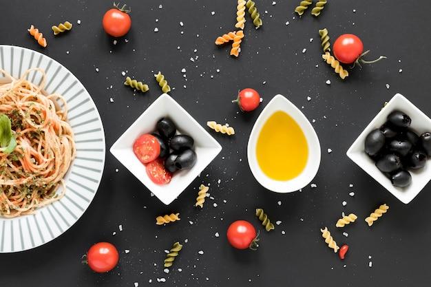 Olive nere; olio; pomodorini e gustosi spaghetti in pasta disposti su uno sfondo nero