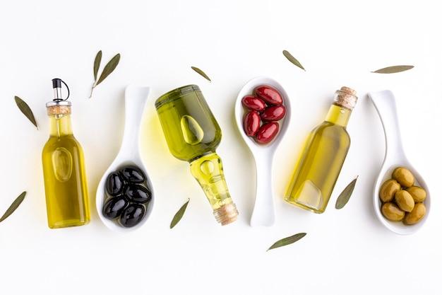 Olive nere rosse gialle piane in cucchiai con foglie e bottiglie di olio