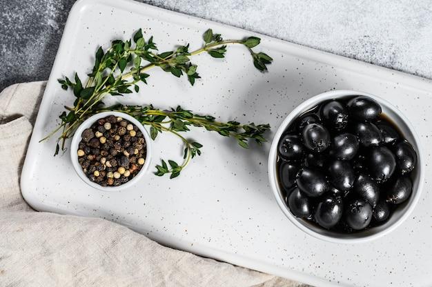 Olive nere su un tagliere bianco. sfondo grigio. vista dall'alto