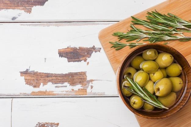 Olive verdi in ciotole di legno sul tavolo di legno
