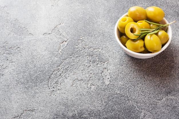 Olive verdi in ciotole sul tavolo scuro