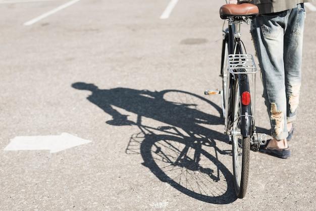Ombra dell'uomo che cammina con la bicicletta sull'asfalto