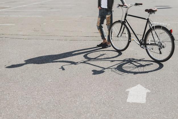 Ombra dell'uomo che sta con la bicicletta sulla strada