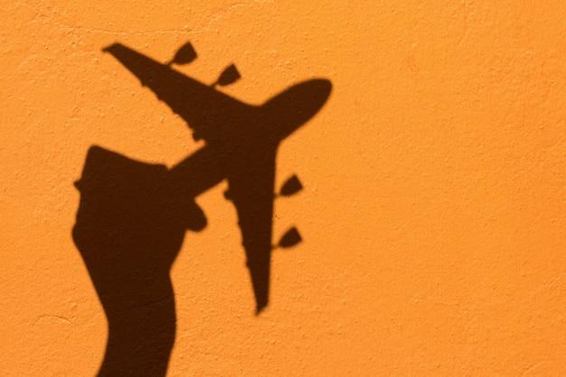 Ombra della mano che tiene il modello dell'aeroplano sul fondo della parete arancione