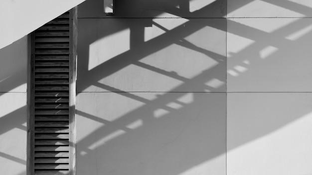 Ombra della scala dell'uscita di sicurezza sulla parete del cemento bianco - priorità bassa astratta