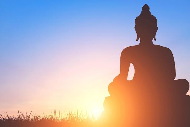 Ombra della statua del buddha su sfondo dorato cielo al tramonto