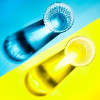 Ombra di bicchieri di acqua chiara su sfondo blu e giallo