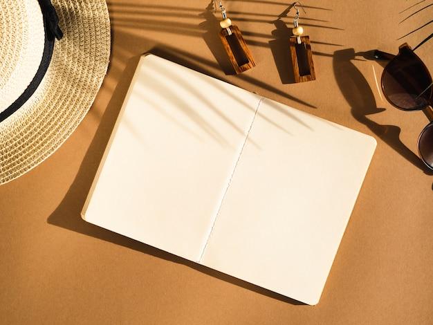 Ombra di foglia di palma con occhiali da sole neri e taccuino bianco