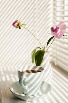 Ombra di tapparelle sulla tazza di caffè e vaso di fiori