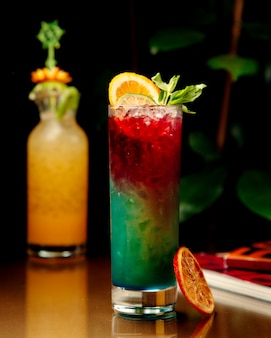 Ombre cocktail guarnito con fettine di arancia e lime