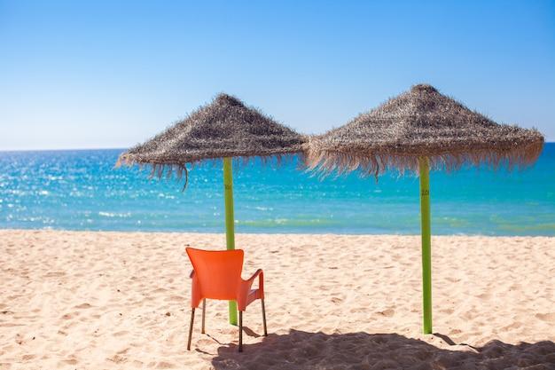 Ombrelli di paglia alla spiaggia tropicale vuota sulla costa atlantica
