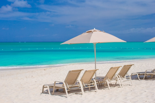 Ombrelli e lettini bianchi alla spiaggia tropicale