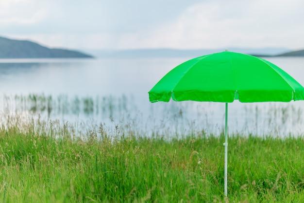 Ombrello al neon verde moderno per il sole sulla spiaggia contro il mare