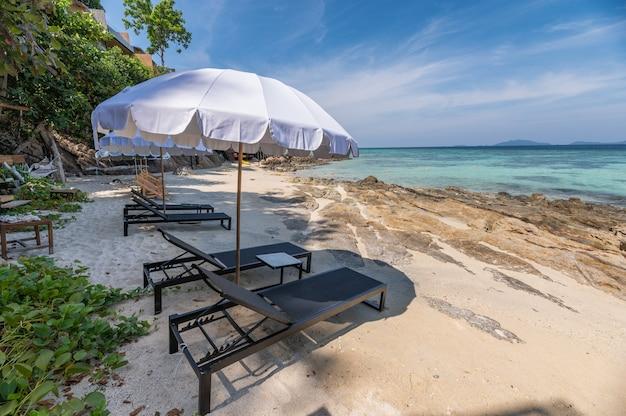 Ombrello con lettino in legno sulla spiaggia bianca al mare tropicale