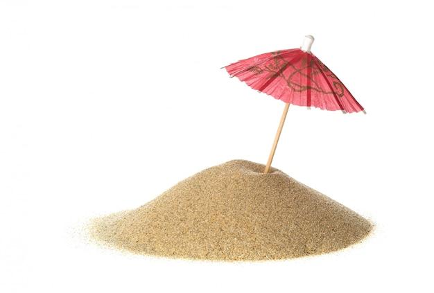 Ombrello del cocktail in sabbia su bianco