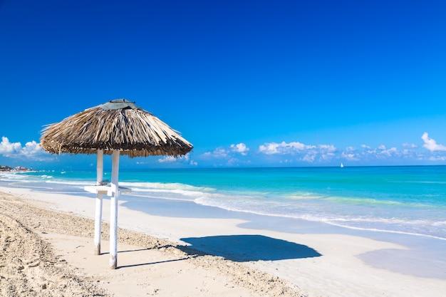 Ombrello di paglia sulla spiaggia vuota della spiaggia a cuba