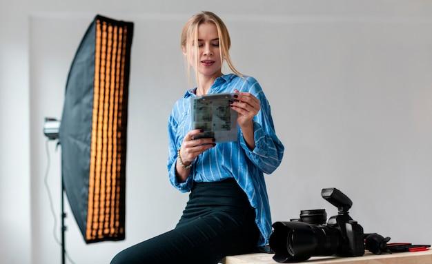 Ombrello e donna di fotografia che esaminano le foto
