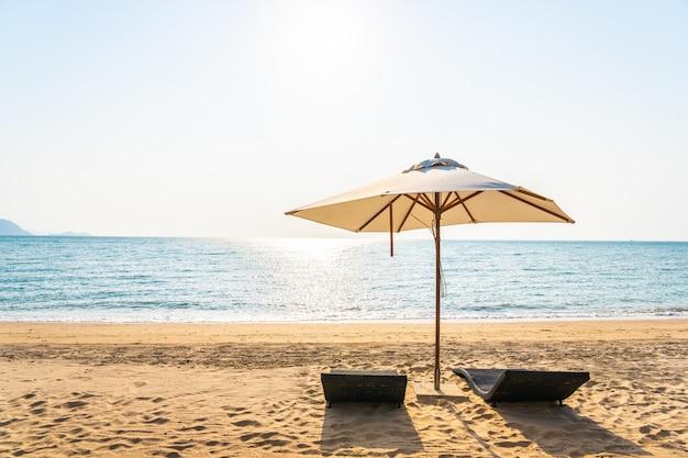 Ombrello e salotto della sedia sulla bella spiaggia mare oceano sul cielo