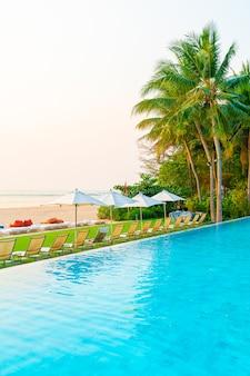 Ombrello e sedia intorno alla piscina con la vista sull'oceano del mare per il concetto di viaggio di vacanza di festa