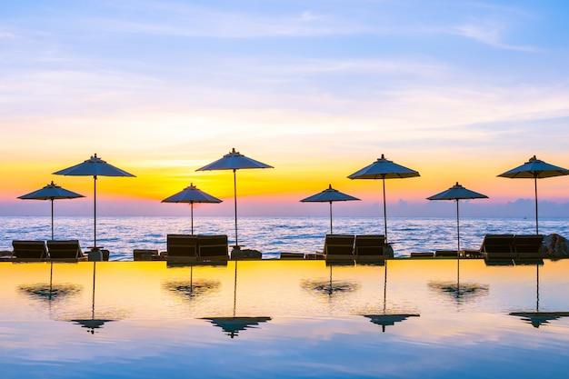 Ombrello e sedia intorno alla piscina in hotel resort per viaggi di piacere e vacanze