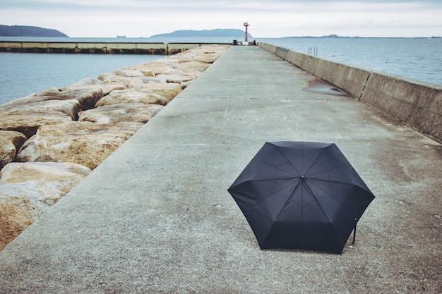 Ombrello nero sulla strada del sentiero. vicino al mare.