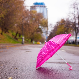 Ombrello per bambini rosa sull'asfalto bagnato all'aperto