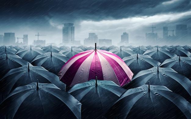 Ombrello rosa e bianco con nuvole tempestose scure.
