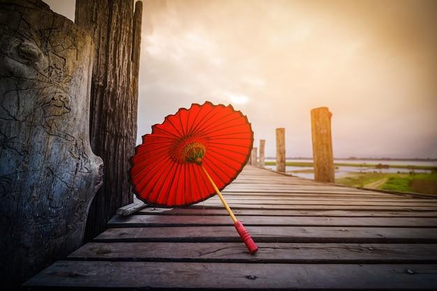 Ombrello rosso sul ponte di u bein su alba a mandalay