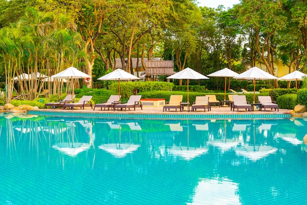 Ombrellone e sedia intorno alla piscina in hotel resort per viaggi di piacere e vacanze vicino mare oceano spiaggia al tramonto o all'alba