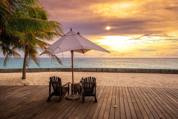 Ombrellone e sedie a sdraio sulla bellissima spiaggia tropicale e mare al tramonto per viaggi e vacanze