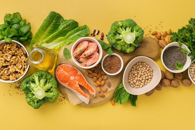 Omega 3 fonti alimentari e omega 6 su sfondo giallo vista dall'alto. alimenti ricchi di acidi grassi tra cui verdure, frutti di mare, noci e semi