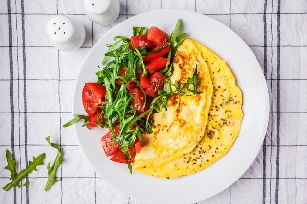 Omelette classica con insalata di pomodori e formaggio sul piatto bianco, vista dall'alto.