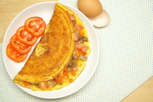 Omelette (omelette, uova strapazzate) con prosciutto, pomodoro, cipolla, carota, funghi champignon