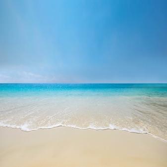 Onda del mare blu sulla spiaggia di sabbia