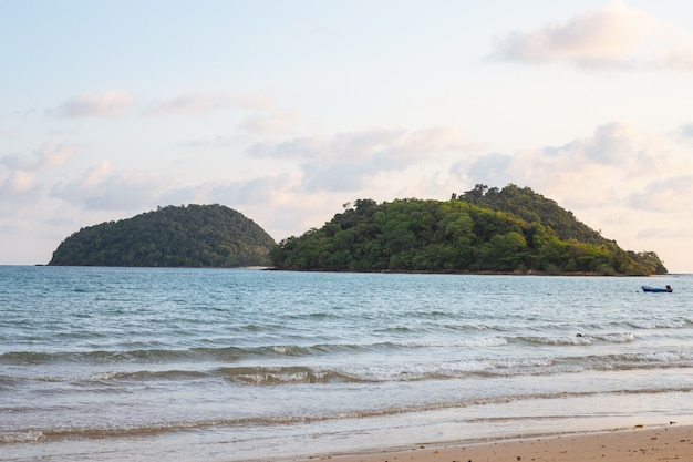 Onda del mare si spostano verso la spiaggia con isole verdi e blu, cielo giallo sullo sfondo.