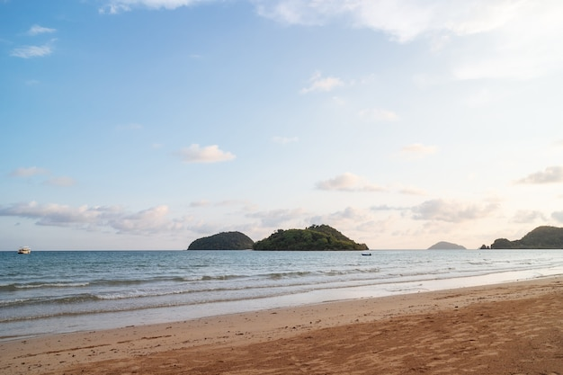 Onda del mare si spostano verso la spiaggia con isole verdi e blu