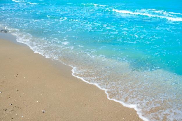 Onda di acqua blu sulla sabbia della spiaggia