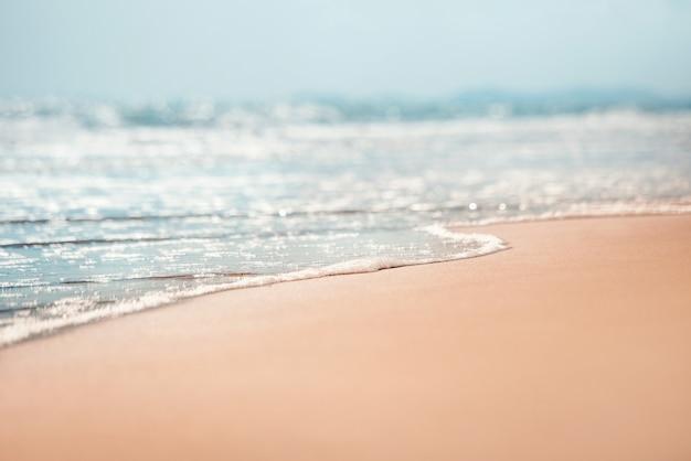 Onda molle del primo piano del mare sulla spiaggia sabbiosa.