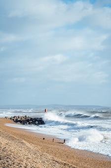 Onde che lavano la spiaggia sabbiosa durante tempo nuvoloso
