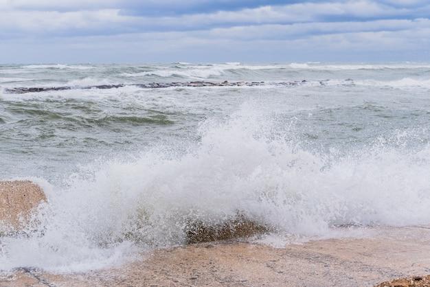 Onde coraggiose del mare adriatico battendo contro la diga sul lungomare di bari, in italia