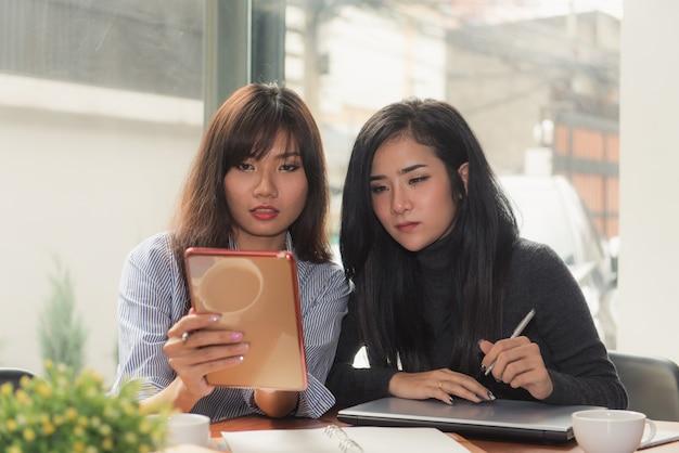 One-on-one meeting.two giovani donne d'affari seduti a tavola in caffè. la ragazza mostra informazioni sul collega sullo schermo del computer portatile. ragazza utilizzando smartphone blogging. riunione di lavoro di squadra. liberi professionisti che lavorano.