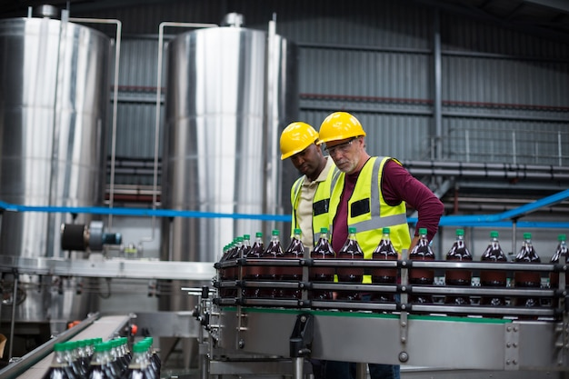 Operai che controllano le bottiglie fredde della bevanda nell'impianto di produzione delle bevande